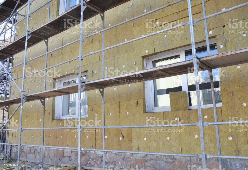 External wall insulation. Solid wall insulation. Energy efficiency house wall renovation for energy saving. Exterior house wall heat insulation with mineral wool, building  under construction. stock photo