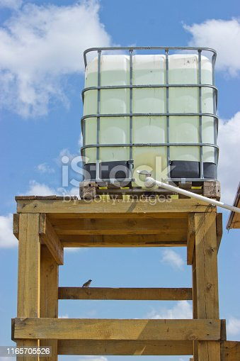 external water tank on a wooden base, water is piped into the house.