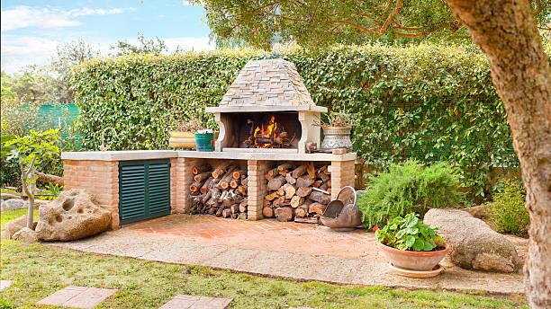 externe holzofen mit brennen feuer brennholz und - grillstein stock-fotos und bilder