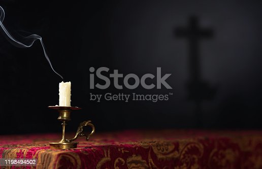 Extinguished candle on a dark background with the silhouette of a cross, selective focus. Copy space.
