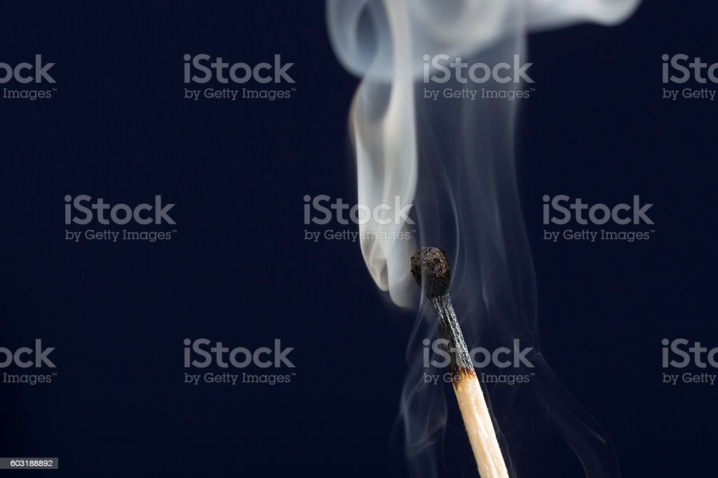 Extinguished match with smoke on dark blue background stock photo