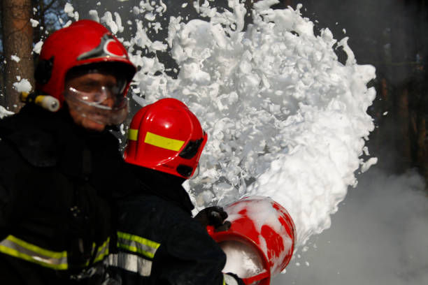 Extinguishing forest fire.Firefighter extinguishes a fire.Extinguishing the fire.  Fill the foam with a fire. Resolute firefighters. Extinguishing forest fire.Firefighter extinguishes a fire.Extinguishing the fire.  Fill the foam with a fire. Resolute firefighters. extinguishing stock pictures, royalty-free photos & images