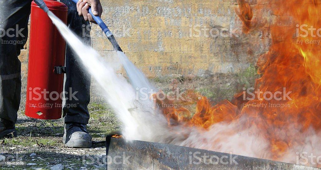 Extinguishing with powder type fire extinguisher stock photo