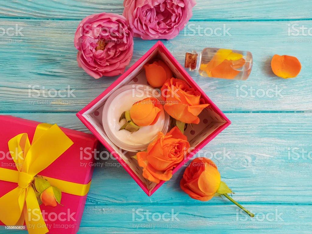 extract, essence gift box cosmetic cream fresh orange rose on a blue...