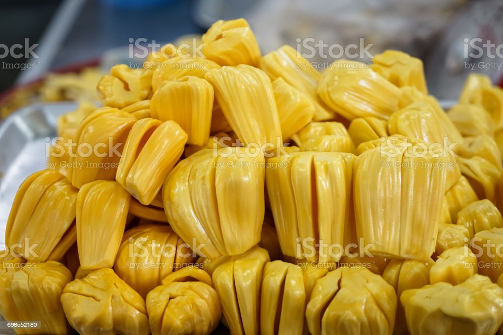 Extracted flesh jackfruit in bright yellow color selling on metal tray in local market with blurred background stock photo