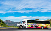istock Extranomical Tours agency tour bus drives with tourists and visitors on mountain road on the way to Yosemite National Park under beautiful sky 1198961013