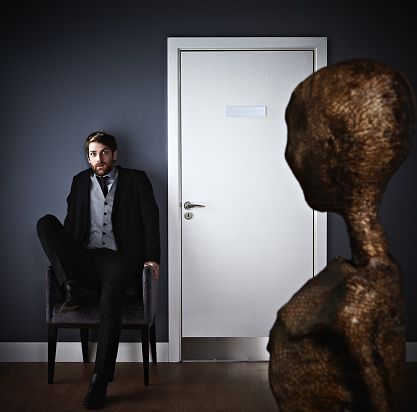 Extraterrestrial looking at scared man.