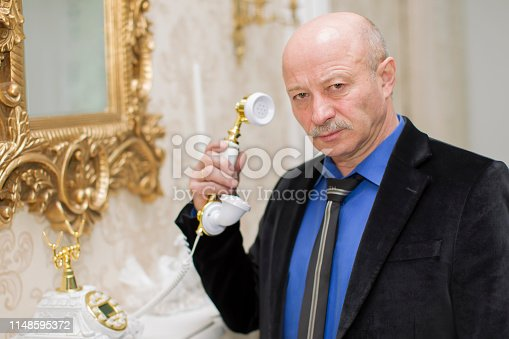 Extravagant elderly man with a retro phone