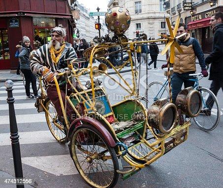 istock Extravagant senior rickshaw drives his unique vehicle in Paris, France. 474312556