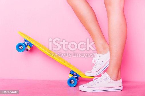 Conceptual shooting of girl's feet standing on the skateboard