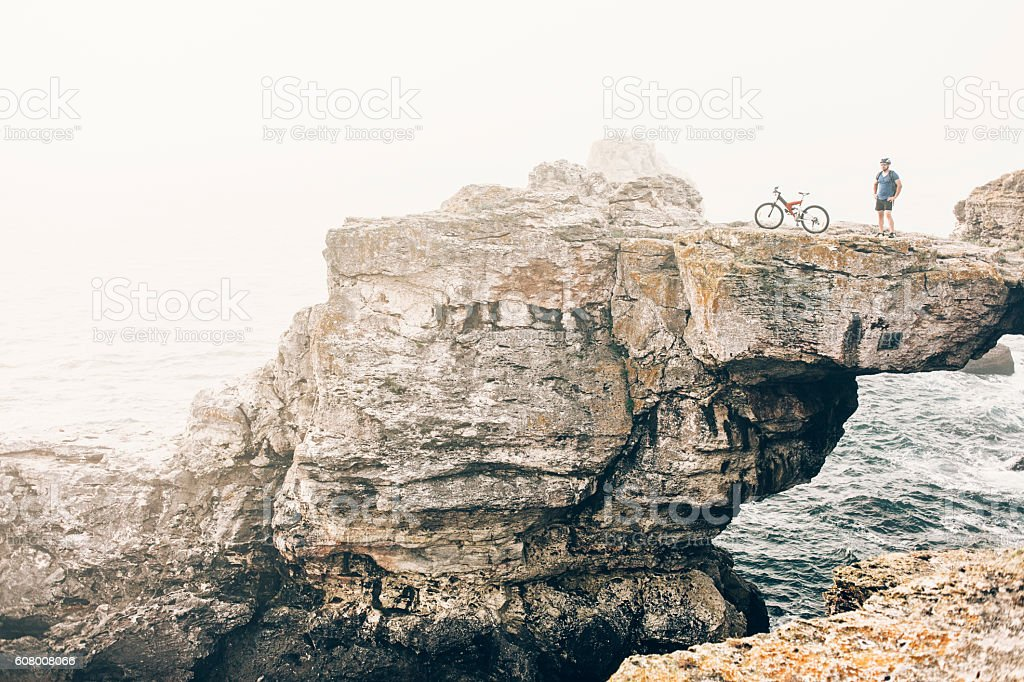 Extreme biker standing on top of the cliff stock photo