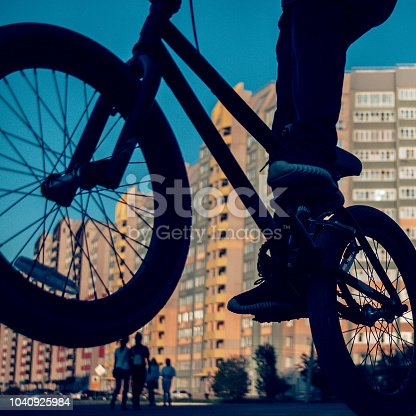 Extreme BMX Freestyle Riding. Blurred Sunset Cityscape, Passersby.