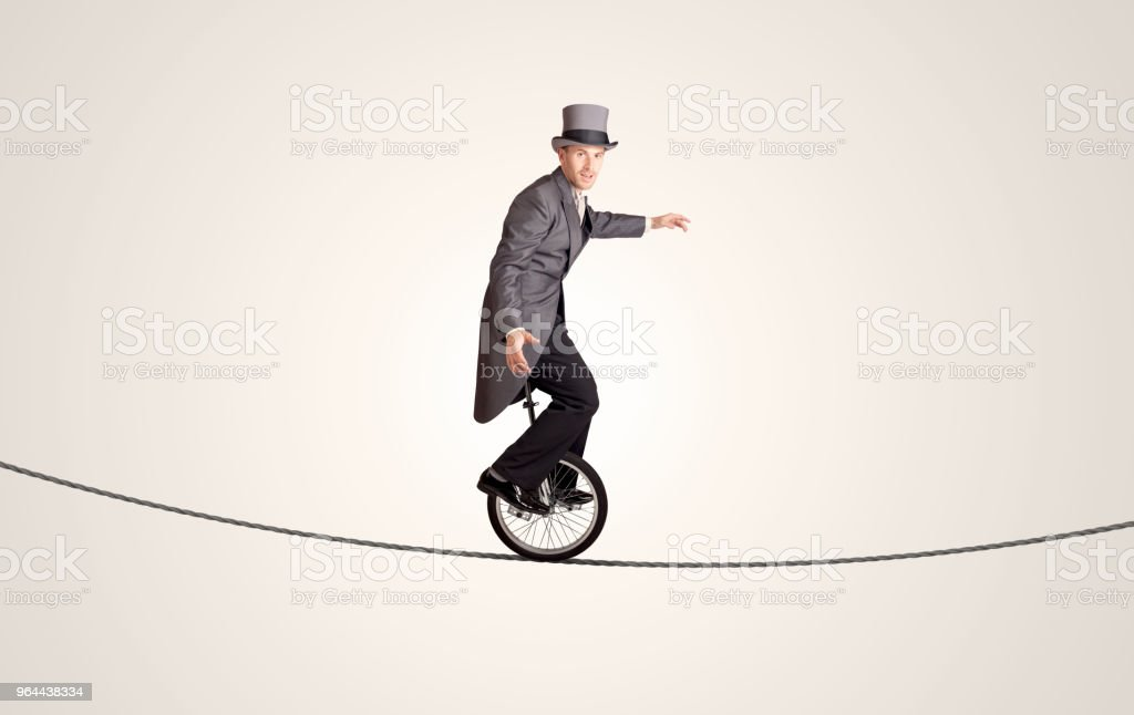 Extreme business man riding unicycle on a rope - Royalty-free Acrobat Stock Photo