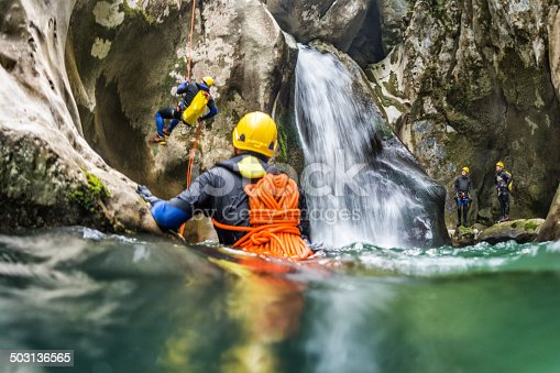 Shot from the water of extreme canyoning team members in the mountain cave.
