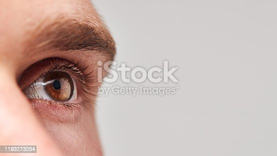 Extreme Close Up Of Eye Of Man Against White Studio Background
