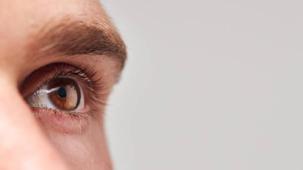 Extremo primer plano de ojo del hombre contra fondo de estudio blanco - foto de stock
