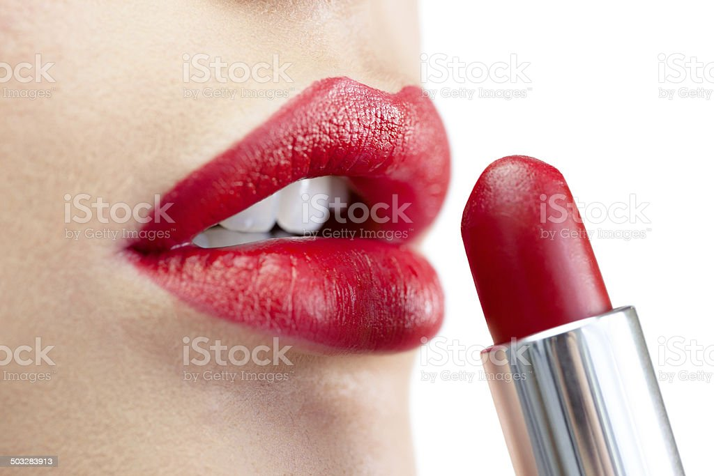Extreme close up on model applying red lipstick stock photo