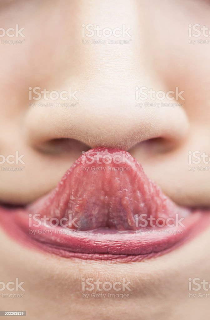 Extreme close up on woman touching nose with her tongue stock photo