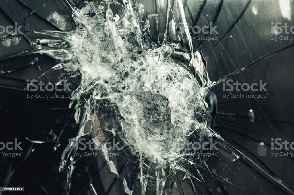 Extreme close-up glass window shattered during violent attempted robbery stock photo
