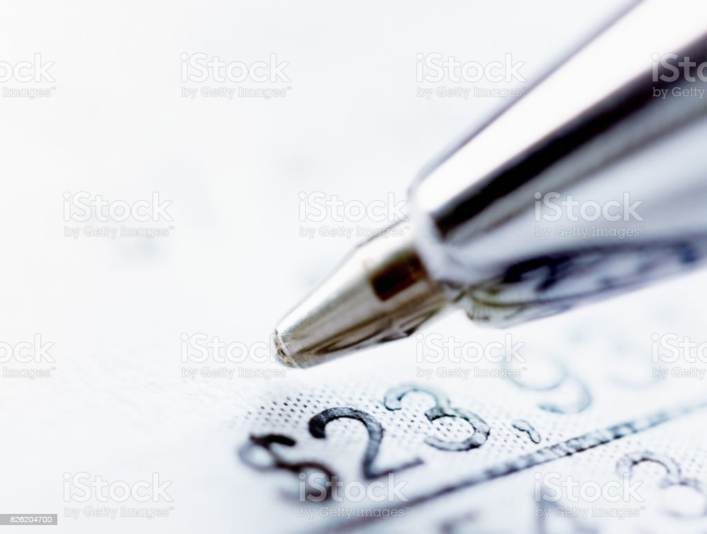 Extreme close-up of ballpoint pen and document with dollar amounts stock photo