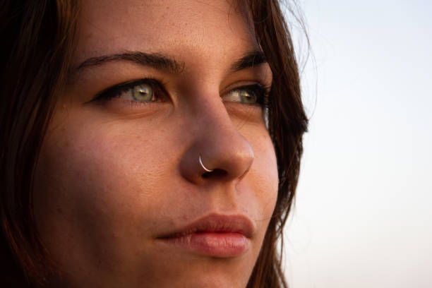 Extreme closeup of beautiful girl with green eyes and piercing on nose stock photo