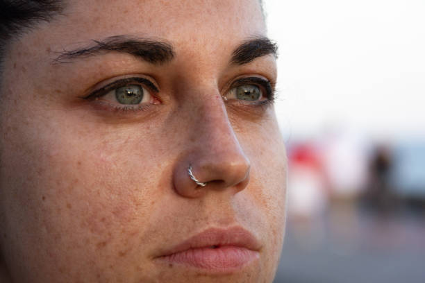 Extreme closeup of girl with freckles on face, green eyes and piercing on nose stock photo