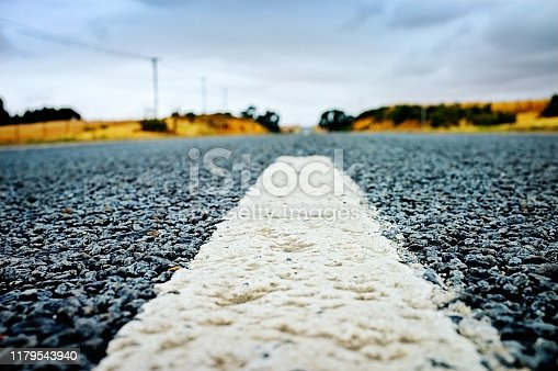 Ground-level macro shot of white line painted on tarred road.