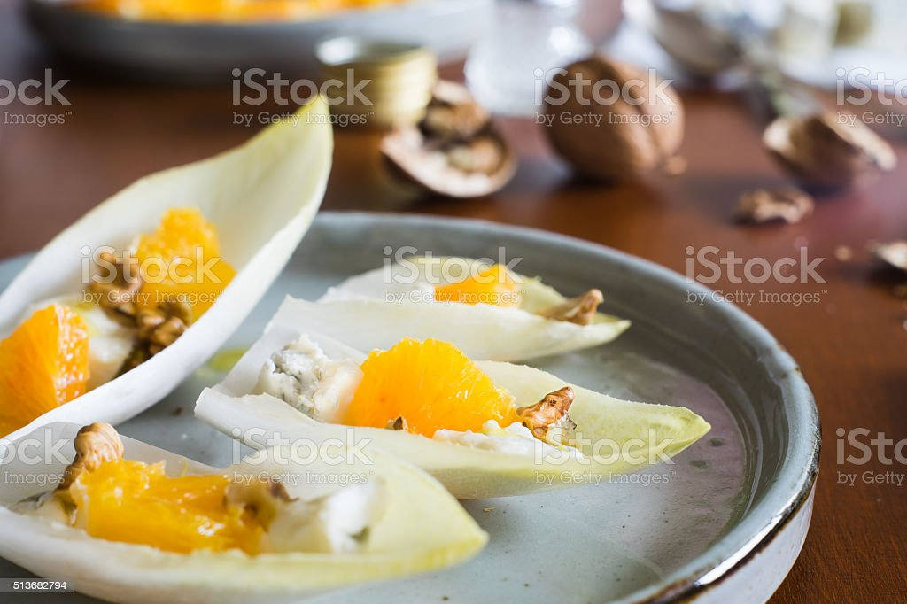Extreme close-up of starter with endive, orange, cheese and walnuts stock photo