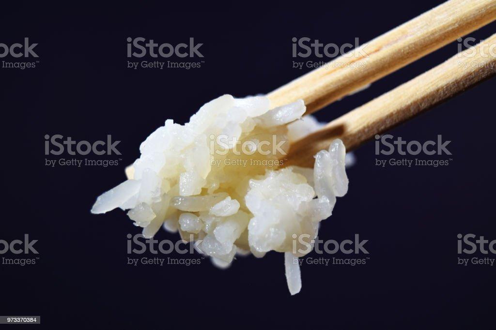 分離した黒い背景に白いご飯を保持している木製箸の極端なクローズ アップ (マクロ) ストックフォト