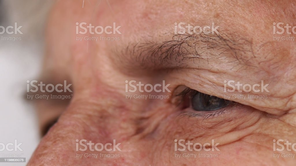 Extreme close-up shot of sad blue eyes on wrinkled female face...