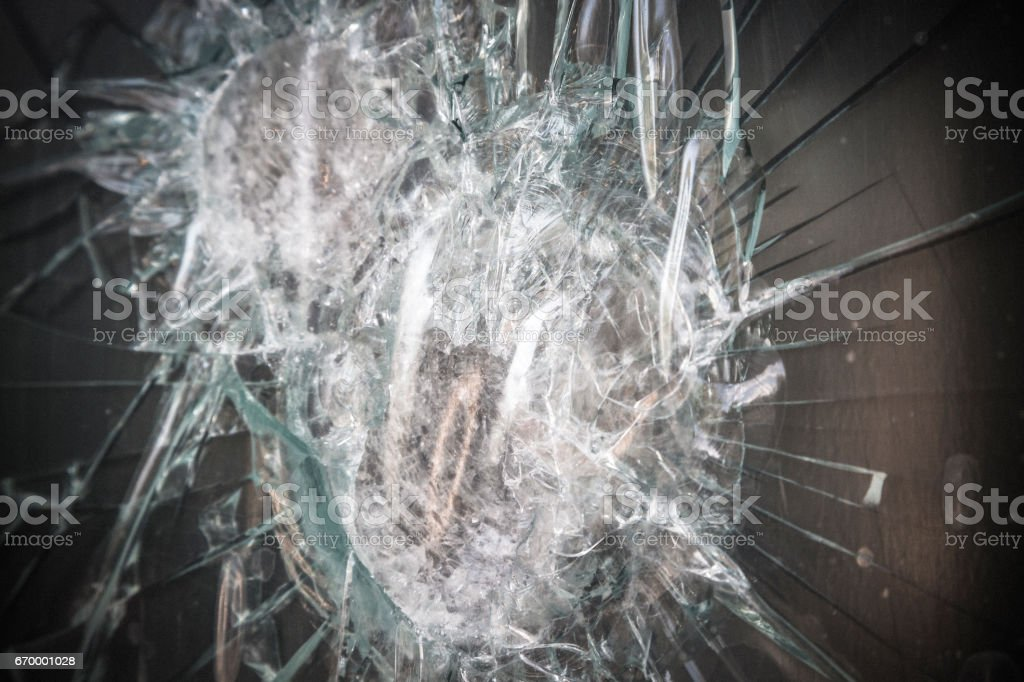 Extreme close-up strengthened glass smashed during violent attempted robbery stock photo