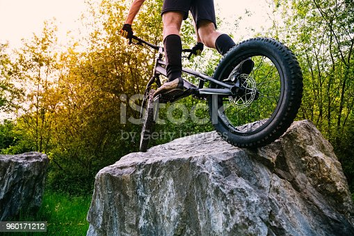 Cyclist legs on a trial bycicle up on a rock at sunset. Concept of extreme sport