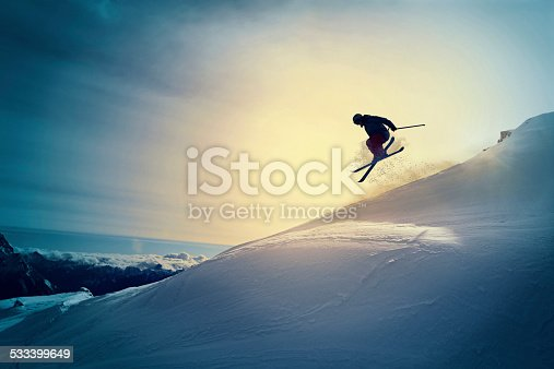 Off pist,  back country skiing.  Extreme skiing. Silhouette. Freestyle skier jumping in the air. Beautiful nature in a sunset time. Powder snow. Alps mountains snowy landscape. Cortina d'Ampezzo, Italy ski resort. Queen of the Dolomites.