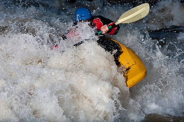 extreme kayaking A white water kayaker plays on a wave in the Animas River, Southern Colorado. animas river stock pictures, royalty-free photos & images
