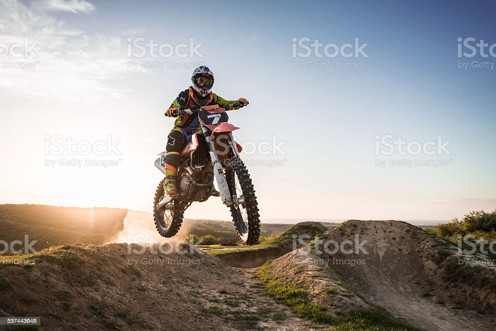 Extreme motorcyclist riding dirt bike off-road at sunset. stock photo