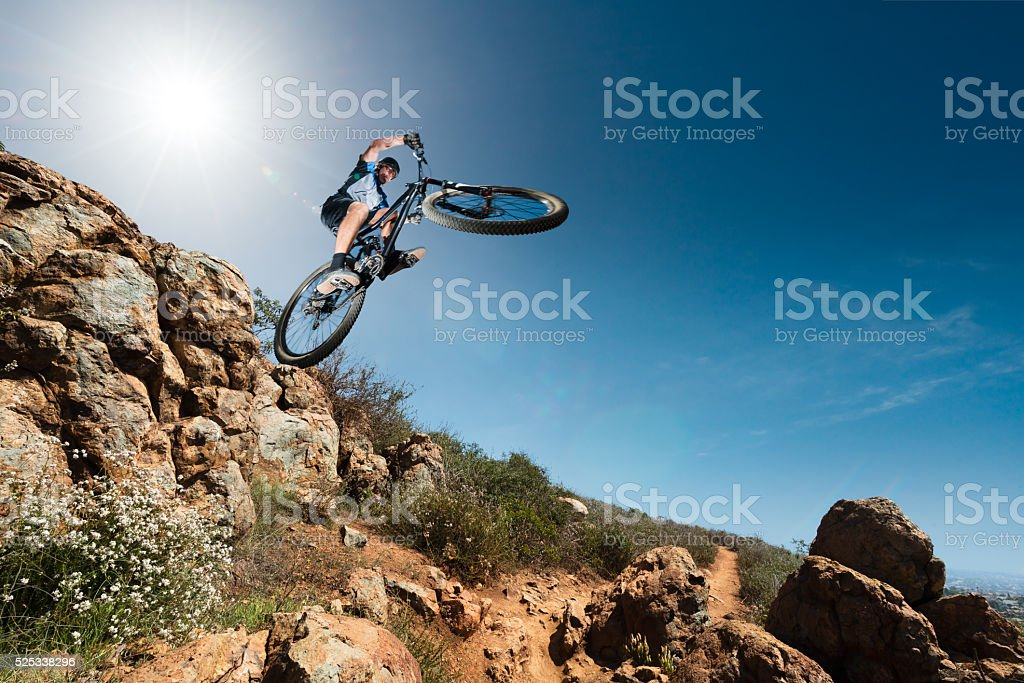 Extreme Mountain Biker Jumping Off A Cliff stock photo