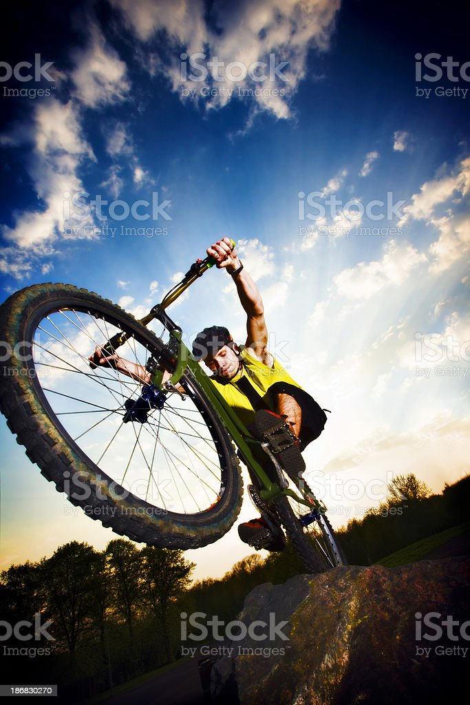 Extreme mountain biking jumping off a rock royalty-free stock photo