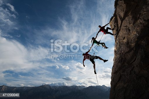 Three rock climbers helping one from falling in a dramatic setting
