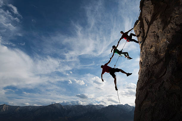 extreme rappelling Three rock climbers helping one from falling in a dramatic setting  passion stock pictures, royalty-free photos & images
