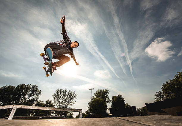 Extreme skateboarder in Ollie position against the sky. stock photo