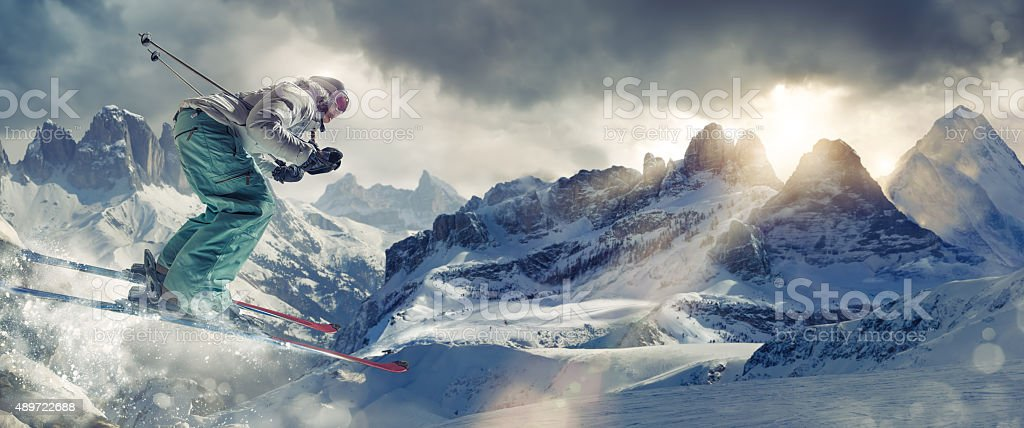 Extreme Skier in Mid Air Over Mountains Peaks At Sunset stock photo
