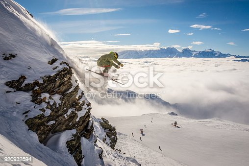 A male skier jumping off a rock, Verbier in the Swiss alps.