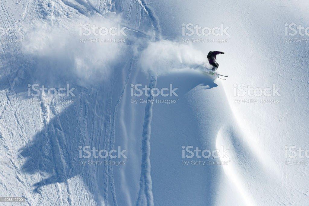 Extreme skier riding fresh powder snow downhill stock photo