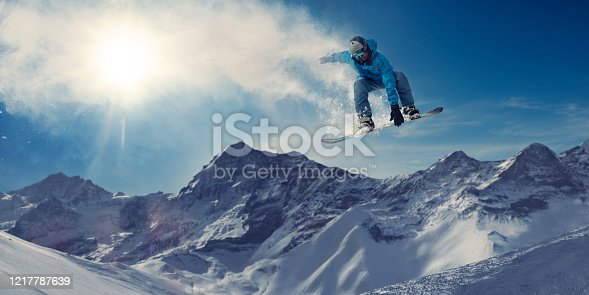 A male snowboarder in mid air during an extreme high jump in a generic location with snow covered mountains on bright day. The snowboarder is wearing blue toned snow-roof trousers and jacket, safety helmet and goggles. He leaves a snow vapour trail behind him, which the sun is visible through.
