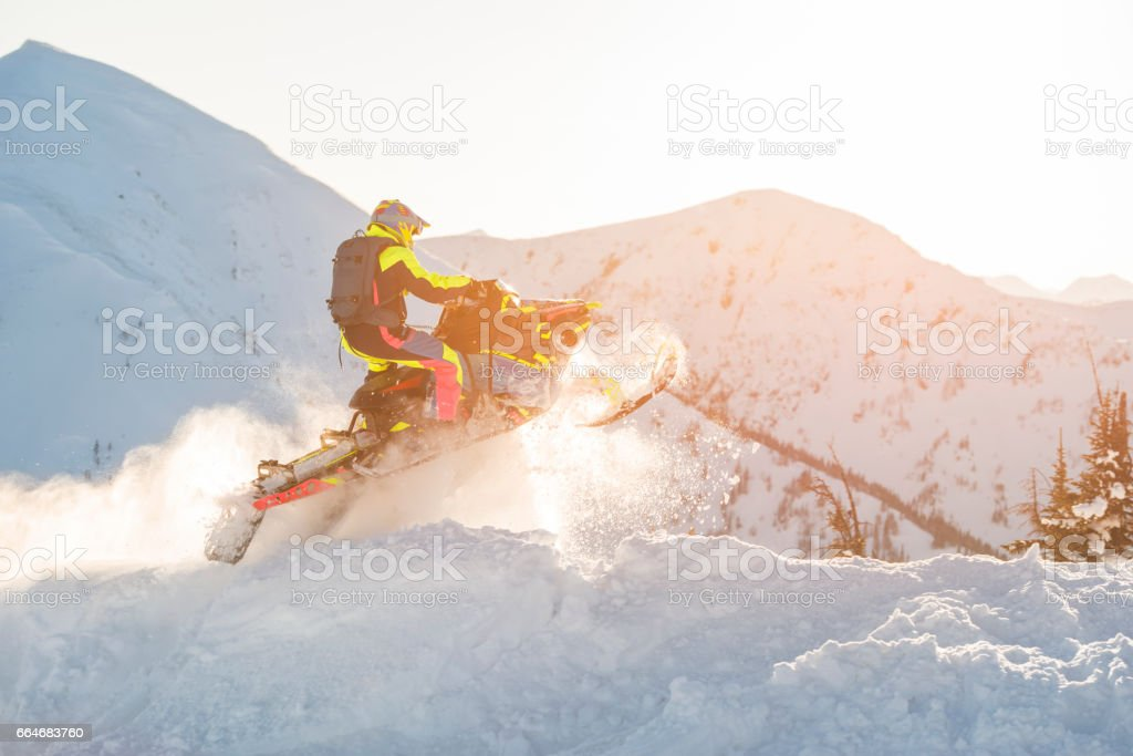Extreme snowmobiling on top of the mountains. stock photo