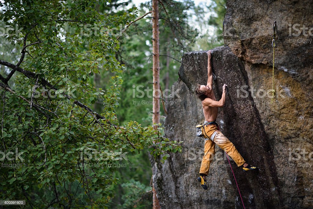 Extreme sport climbing. Young male rock climber. stock photo