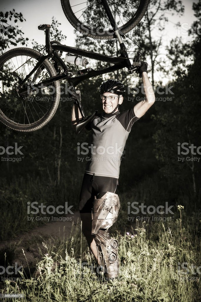 Extreme Sport: Mature cyclist with bionic leg exhibits victory. stock photo