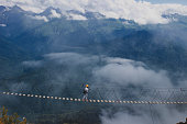 people walk on the suspension bridge over the cliff in 2000 m. next to them, light clouds,which give the picture even more focusцель
