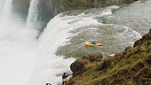 Extreme sportsman kayaking down a waterfall.