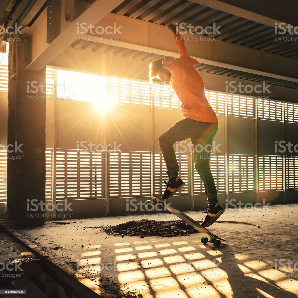 Extreme street sport. Hipster man jumping and riding on skateboard at...